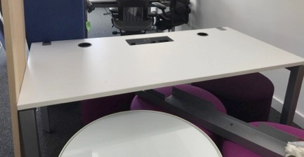 Frame One meeting table with white laminate tops with central power bar installed